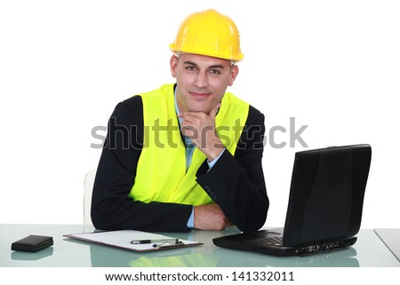 Engineer sitting with a laptop - stock photo