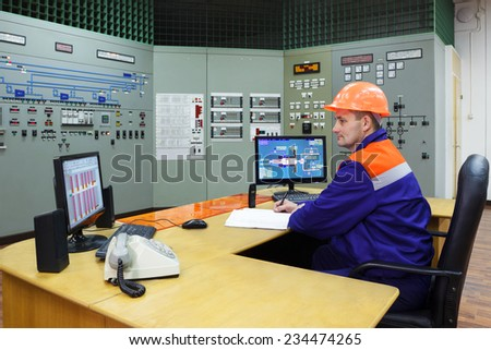 Engineer sitting writes in log on main control panel of gas compressor station  - stock photo