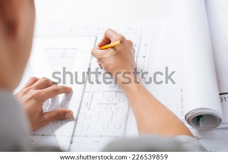 Engineer sketching construction project, view over his shoulder - stock photo