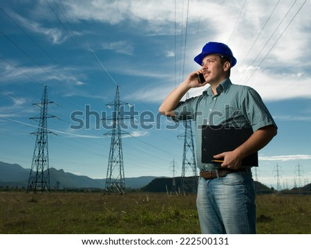 engineer standing on field with electricity towers, talking on the phone - stock photo