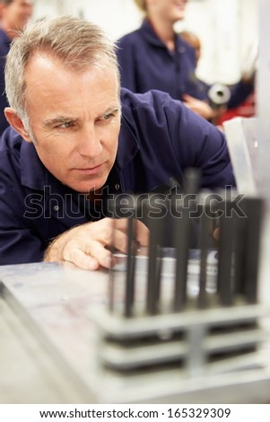 Engineer Studying Component In Workshop - stock photo