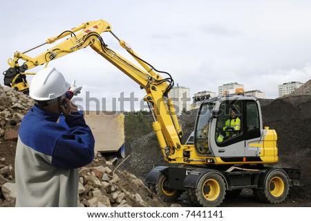 engineer supervising digger, bulldozer and driver - stock photo