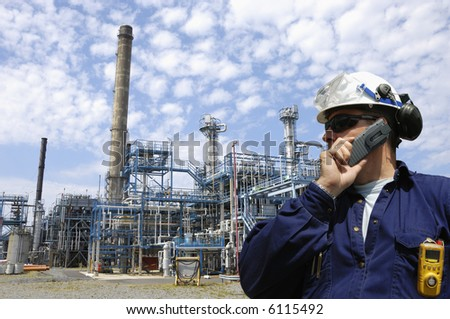 engineer talking in mobile-phone, large oil refinery in the background showing pipelines and towers