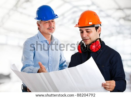 Engineer talking to a worker in a construction site - stock photo