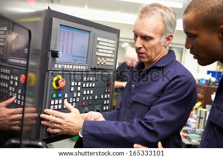 Engineer Teaching Apprentice To Use Computerized Lathe - stock photo