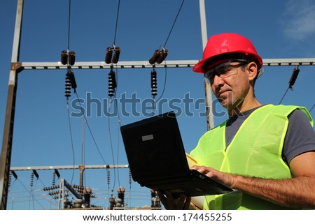 Engineer Using Laptop at an Electrical Substation.Engineer with personal protective equipment typing on the computer keyboard. - stock photo