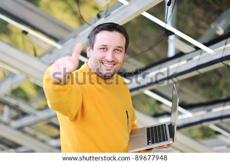 Engineer using laptop at factory - stock photo