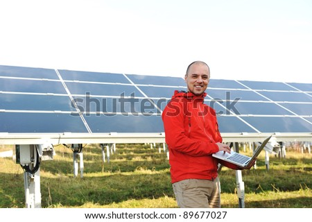 Engineer using laptop, solar panels in background - stock photo
