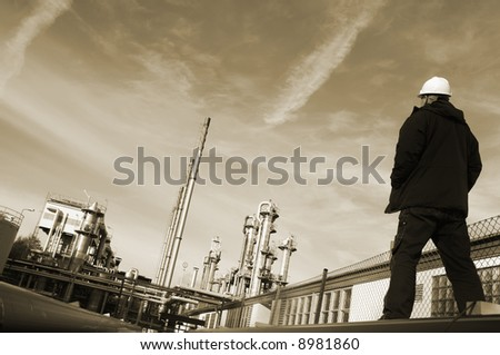 engineer wearing hard-hat overlooking large oil and gas refinery, brownish toning concept - stock photo