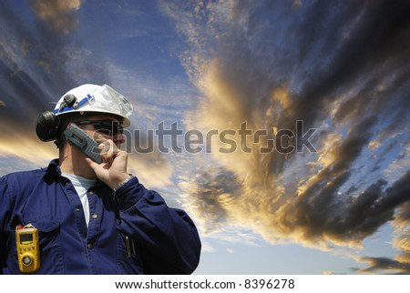 engineer wearing hard-hat set against a dramatic sunset sky, conceptual industrial