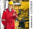 Engineer, wearing overalls, hard hat and safety goggles, posing in front of a huge hydraulic engine, holding a wireless communication device in his hand - stock photo