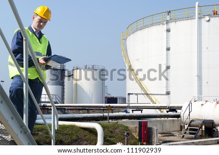 Engineer with a clipboard taking notes of the quality and state of oil silos of a petrochemical industry for safety reasons - stock photo