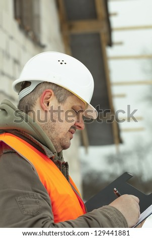 Engineer with a folder near the new building - stock photo