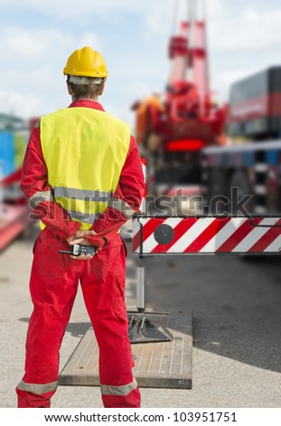 Engineer with a radio behind his back supervising the construction works on a rig - stock photo