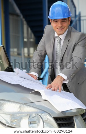 Engineer with architectural plans - stock photo
