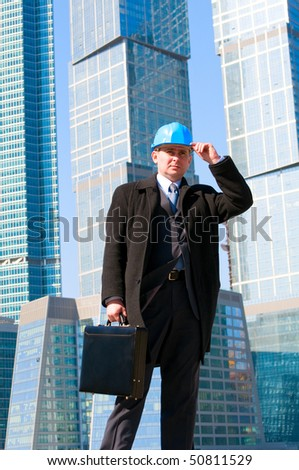Engineer with blue hard hat holding briefcase on skyscrapers background - stock photo