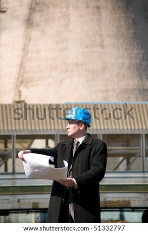 Engineer with blue hard hat holding drawing near train - stock photo