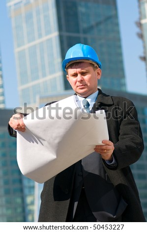 Engineer with blue hard hat holding drawing on skyscrapers background - stock photo