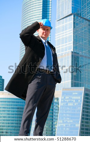 Engineer with blue hard hat near skyscrapers - stock photo
