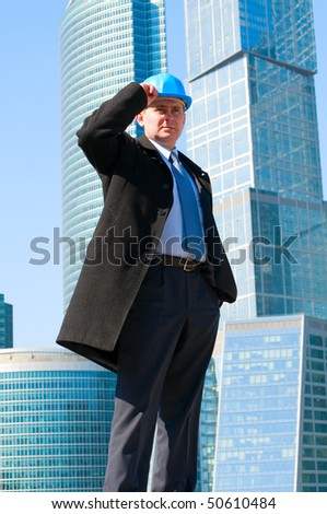 Engineer with blue hard hat on skyscrapers background - stock photo