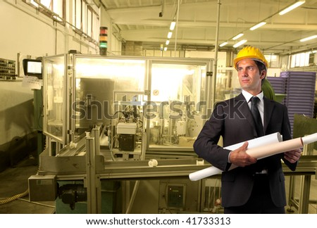 engineer with blue print rolls in a factory - stock photo