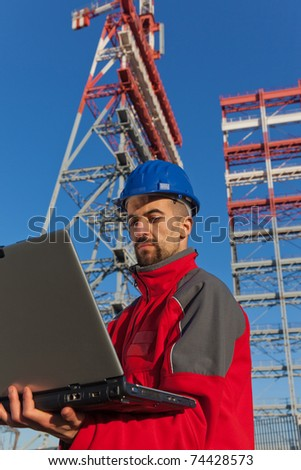 Engineer with Computer in Construction Site - stock photo