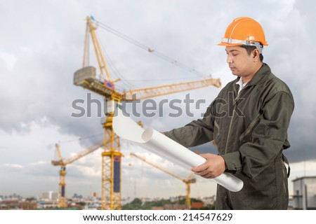 Engineer with hard hat reading blueprint at construction site. - stock photo