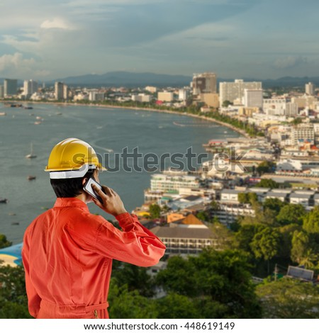 engineer with helmet for workers security on background of the building and skyscrapers in evening time in Pattaya,Thailand. - stock photo