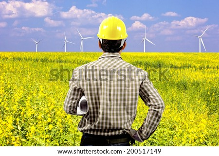 engineer with holding blueprints looking at wind turbines in a flower field eco power concept - stock photo