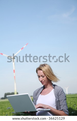 Engineer with Laptop stand at Windturbine and testing Telemetry