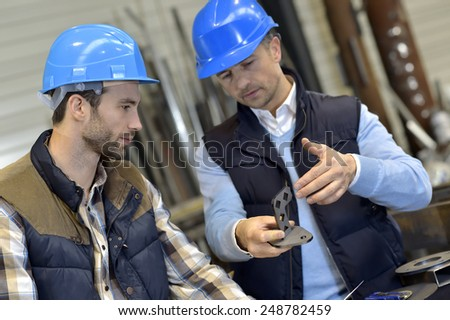 Engineer with mechanical worker checking on production - stock photo