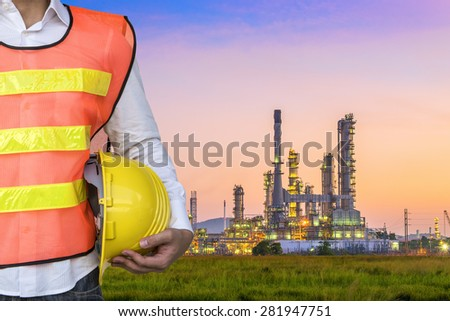 Engineer with Oil refinery plant area at twilight - stock photo