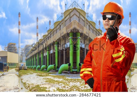 Engineer with radio communication in action for working at cooling tower of Industrial power plant
