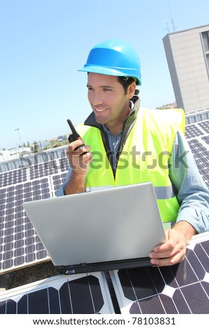 Engineer with walkie-talkie on photovoltaic installation - stock photo