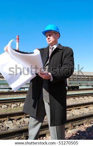 Engineer with white hard hat holding drawing in industrial area - stock photo