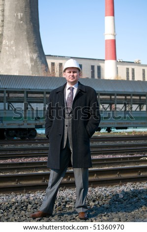 Engineer with white hard hat near industrial area - stock photo