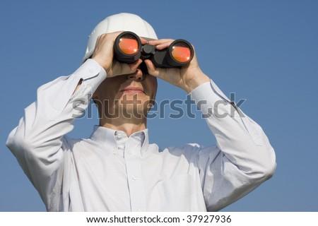 Engineer with white hardhat looking through binocular - stock photo