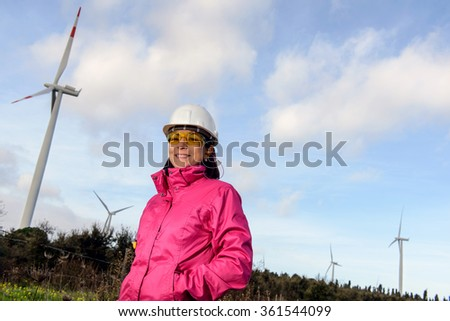 Engineer woman checking production, with laptops, wind turbines on the site. / Woman engineer checking wind turbines. - stock photo