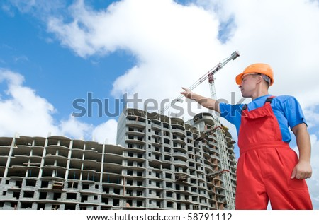 engineer worker directing up with finger to building under construction - stock photo