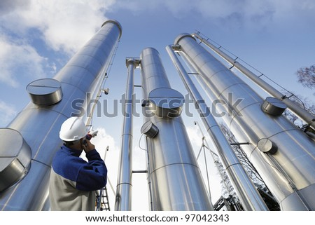 engineer, worker, pointing at giant gas and oil pipes - stock photo