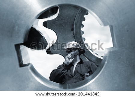 engineer, worker standing inside large gear axle,  engineering and technology concept - stock photo