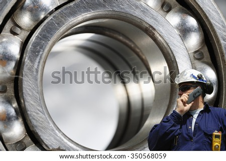 engineer, worker, talking in phone with giant ball-bearing in background, steel industrial - stock photo