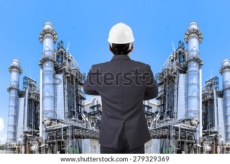Engineer working at equipments and machinery with modern thermal power plant in refinery - stock photo