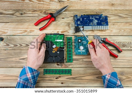 engineer working on broken console repairing circuit board. Computer repair concept workplace. Top view wooden desk. assembly mechanisms chips - stock photo