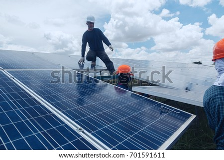 engineer working on checking and maintenance equipment at green energy solar power plan