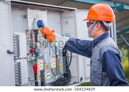 engineer working on checking and maintenance equipment at green energy solar power plant: turn on inverter