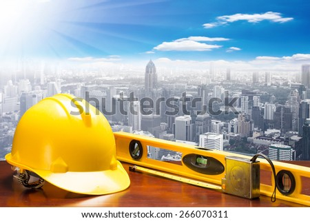 engineer working table and measure tape and level water tool equipment at high building construction site against blue sky with in concept ecology and real estate - stock photo