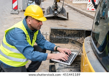 Engineer working typing on his computer. Outdoors - stock photo