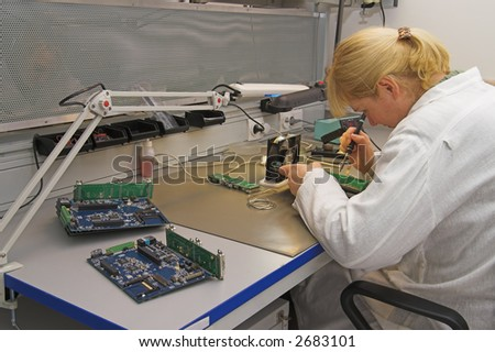 Engineer working with circuits - A woman engineer solders circuits sitting at a table. - stock photo