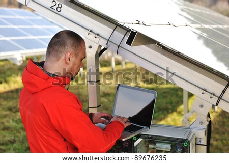 Engineer working with laptop by solar panels - stock photo